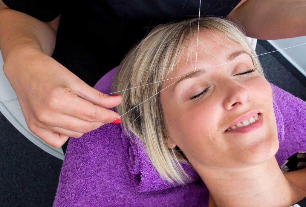 Beautiful blonde woman getting her Boston eyebrow threading service done by an expert beautician at Amaci Salon